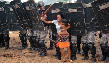 10 Mar 2008, Brazil --- March 10, 2008 - Lagoa Azul 2, Amazonas, Brazil - Amazon indian tribe called Sater-mau battle local police over a land disbute. Five months pregnant indian , Mani Sater, 21, tries to stop troops, from removing her people with her one year old on her hip. The advance of Amazonas state policemen who were expelling the woman and from a privately-owned tract of land on the outskirts of Manaus, in the heart of the Brazilian Amazon. Her husband and 400 other tribe members are squatting on a rural sector between the cities of Itacoatiara and north of Manaus in the state of Amazonas. An group of local natives the Satere took over a property illegally, which is owned by a Japanese citizen who asked the police to intervene in removing the natives from his property. The landless peasants tried in vain to resist the eviction with bows and arrows against police using tear gas | Location: Lagoa Azul 2, Amazonas, Brazil. --- Image by © Luiz Vasconcelos/ZUMA Press/Corbis