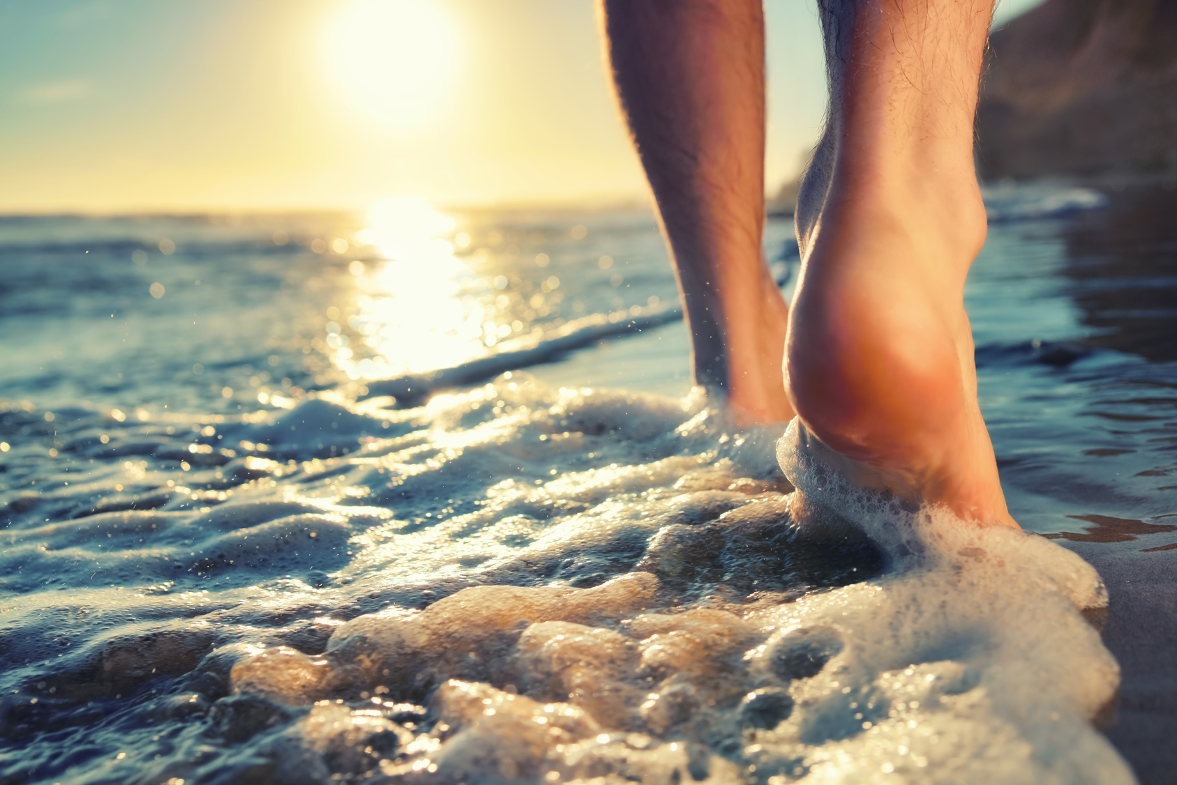 Closeup of a man's bare feet walking at a beach at sunset, with a wave's edge foaming gently beneath them, toned colors