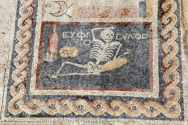 """HATAY, TURKEY - APRIL 20: 2,400 year-old mosaic, discovered during excavations, saying """"Be cheerful, enjoy your life"""" in Ancient Greek language is seen in southern Hatay province of Turkey, on April 20, 2016. Mosaic depicts lying down skeleton with a jorum in his hand together with a wine pitcher and bread. (Photo by Halit Demir/Anadolu Agency/Getty Images)"""